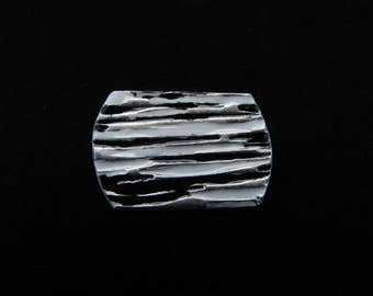 Silver rounded rectangular pin with a rough lined pattern and black and white faux enameling.