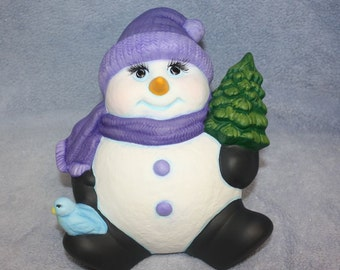 Ceramic Snowman sitting back in a purple hat and scarf and holding a pine tree