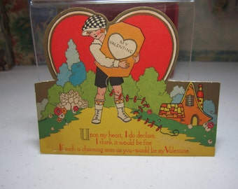 1930's die cut gold gilded art deco valentine boy holds a kite with my valentine written on it  in front of giant red heart, cottage