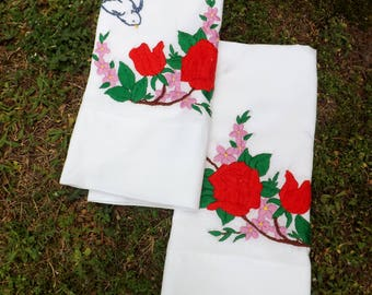 Set of matching his and hers hand embroidered pillowcases  with red roses, pink flowers and bluebirds