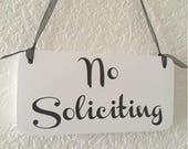 No Soliciting Hanging Sign -  Size 8x4 each with whole and ribbon and round edges. Painted white with black vinyl shown.