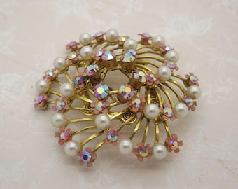 A fine openwork multi flower vintage jewelry brooch in goldtone metal and pink enamel with sparkly rainbow aurora borealis stones and pearls