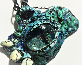 He lurks by the lake hand painted monster eye pendant