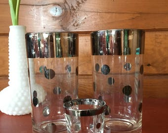 Set of 2 silver rimmed, polka dot highball glasses and one matching shot glass.