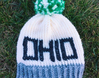 Cream Ohio hat with dark grey letters and green and cream pom pom