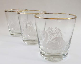 Three short glass tumblers or whiskey glasses. White swan under a willow tree and gold rim.