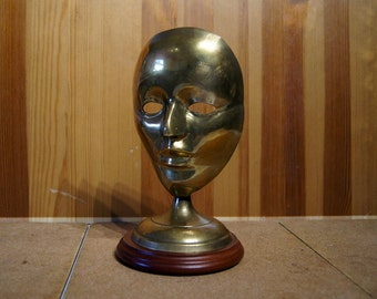Vintage solid brass mask on the wooden stand.