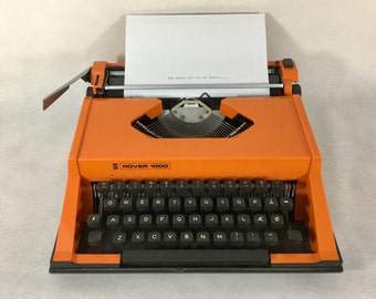 1960's retro orange Italian portable typewriter, model Rover 1000, with QWERTY keyboard plus Æ, Ø, Å characters