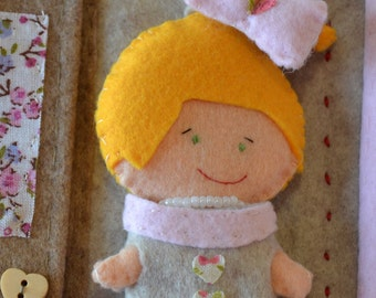 Felt doll. She can wear 1 beige and pink dress and she has bow in hair!