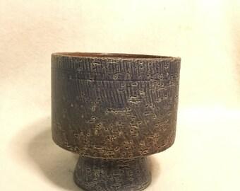 Coarse vintage flower pot, grey brown. Flowerpot on foot