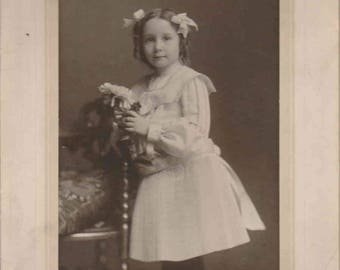 Vintage photograph - Young girl with finger curls, hair bows and pleated skirt