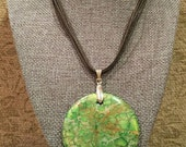 Round green turquoise pendant on a silver bale, on brown waxed cord necklace (16