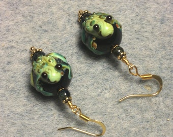 Black and green lampwork frog bead earrings adorned with dark green Czech glass beads.