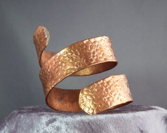 A handmade spiral copper bracelet with textured finish.