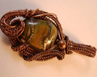 deep red transparent lampwork bead with embedded silver and touches of green wrapped in oxidized copper wire pendant