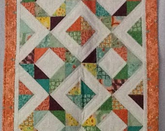 Quilt of peach and turquoise diamonds.  Shimmers with color and at 26X36.5 it will capture any baby's attention.