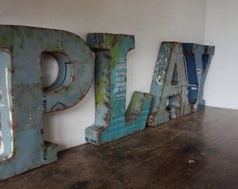 Metal letters spelling 'Play'