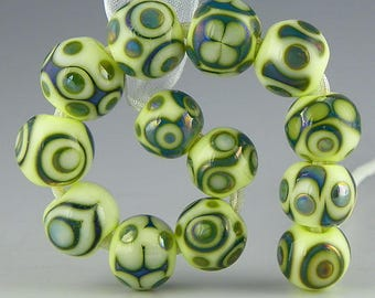a set of 13 small rounds in iridescent teal and pale uranium green handmade lampwork glass beads - A Little Green