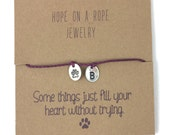 Puppy Love. Sterling silver hand stamped paw print and initial bracelet on cord.