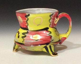 Yellow and red checkered mug with gold circles and dots