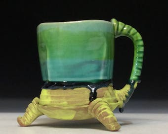 chartreuse and copper green dripping glazed mug with ringed feet and handle