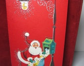 Colorful 1950's-60's Hampshire christmas card shows santa claus emptying mail from a mailbox into a sack under a lamp post,silver glitter
