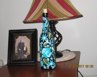 Green Wine bottle with aqua blue and white pansies green leaves as well as aqua blue and white baby breath lights inside