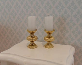 2 gold colored candlesticks with candles