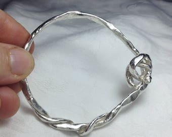 Twisted and knotted sterling silver bangel with tiny shell