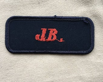 "J.B. A navy blue work shirt name patch that says ""J.B."" in red script"