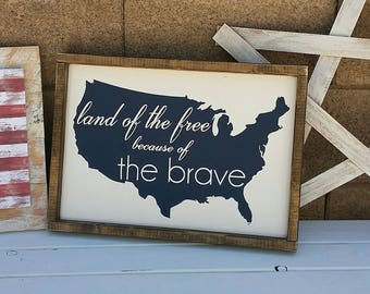 Land of the free, because of the brave. 19.5 x 13.5 distressed wood sign. white with navy.