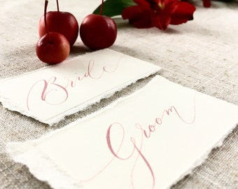 Dusky blush pink wedding place names on torn watercolour paper