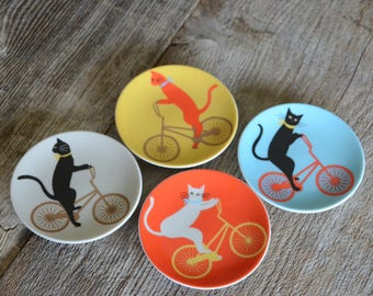 Jewel, Cats on bikes on china plates, Set of four.