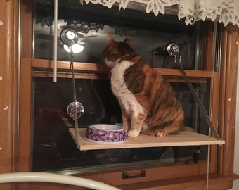 """Cat Shelf attaches to window surfaces with heavy duty suction cups Gives your cat an elevated 10"""" x 20"""" shelf with a window view"""