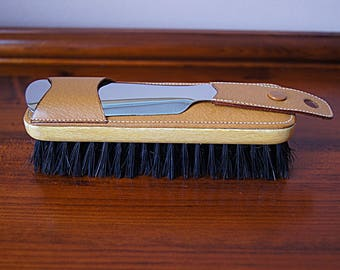 Brush with a shoe horn covered with artificial leather.
