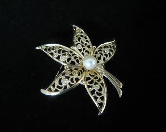 Filigree Openwork Floral Brooch- goldtone, has center faux mounted pearl. Five graceful pedals and stem. Amazing piece. Mothers' Day Gift!