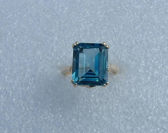 Emerald cut octagon shaped synthetic blue Topaz set in 10 carat yellow gold. On Sale-Synthetic blue Topaz and gold ring