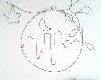 View of a city and its buildings at night - landscape in wire, a skyline under the Moon and stars