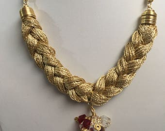 Gold braided necklace with transparent beads and red cubes.