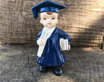 Vintage Graduate statue wearing blue robe holding diploma and stack of books