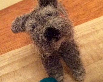 Needle felted fibre art sculpture of a schnauzer with his ball