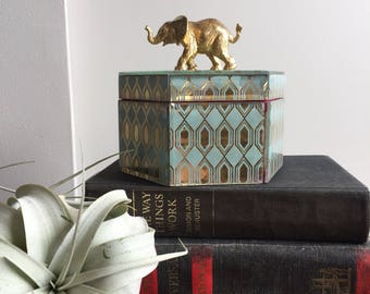 Jewelry box with gold elephant topper.