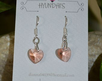 These earring's are a light orangery pink glass heart,with a extra loop on a silver plated earring hook!
