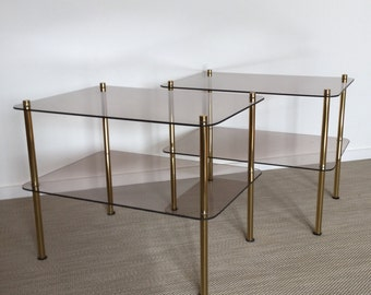 Set of two smoked glass tables with brass-colored frame from the 70s
