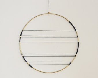 Delicate, minimalistic and modern brass wall hanging
