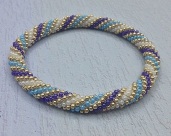 Purple, Gold and Blue Nepal roll on Bracelet. Glass seed bead roll on bracelet.