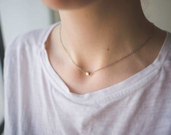 A silver choker like necklace with a small golden cube pendent, cube charm, silver jewelry, boho style