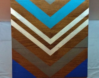 Stained geometric wood sign with blue gray and white arrow stripes