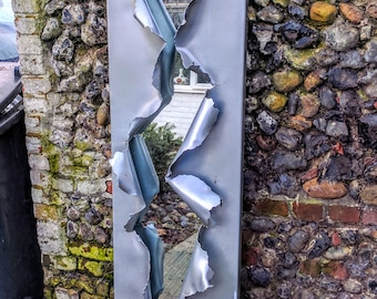 Mirror made from steel then sprayed to a brushed metalic fnish. This is a stunning large modern art piece