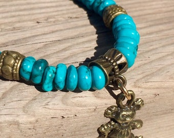 Turquoise Dyed Howlite 5mm beaded stretch bracelet with Antique Brass Spacers and a Dangling Dancing Bear